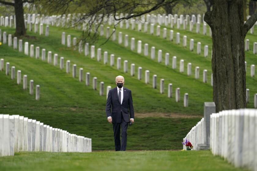 President Biden walks amid tombstones at Arlington National Cemetery.