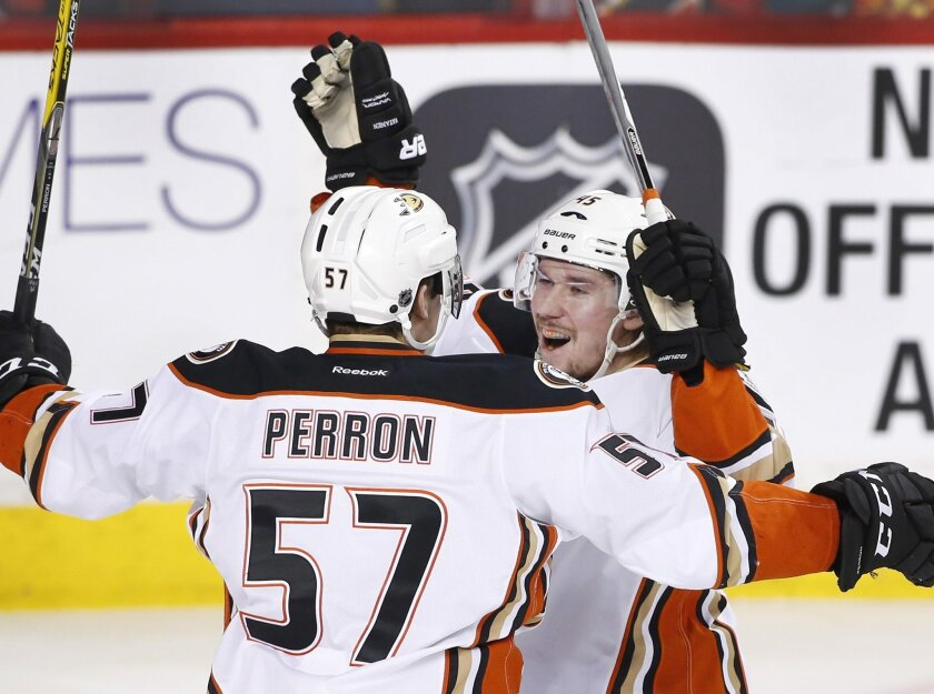 Anaheim Ducks' Sami Vatanen, right, from Finland, celebrates with David Perron his goal against the Calgary Flames' during second period NHL action in Calgary, Alberta, Monday, Feb. 15, 2016. (Larry MacDougal/The Canadian Press via AP) MANDATORY CREDIT