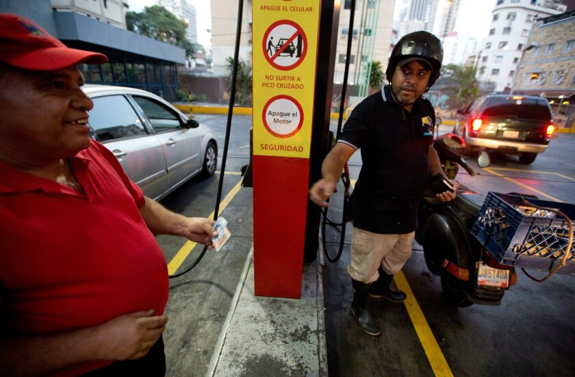 A motorcyclist pays about two Bolivars (3 cents of a dollar) after filling his scooter's tank at a gas station in Caracas, Venezuela, Wednesday, Feb. 17, 2016. Venezuela's government is raising gasoline prices sixtyfold, the first increase of any kind in more than 17 years as the country struggles