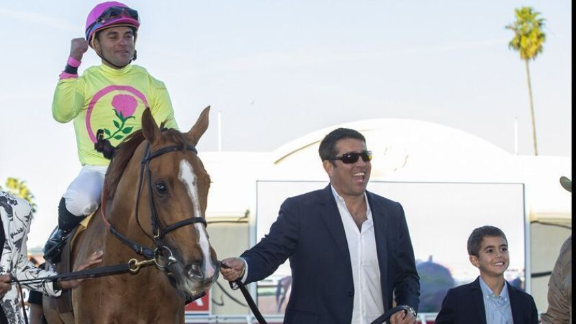 Sol Kumin of Head of Plains Partners (right) leads Uni and jockey Joel Rosario into the winner's circle after their victory in the Grade I, $300,000 Matriarch Stakes on Sunday at the Del Mar Thoroughbred Club.