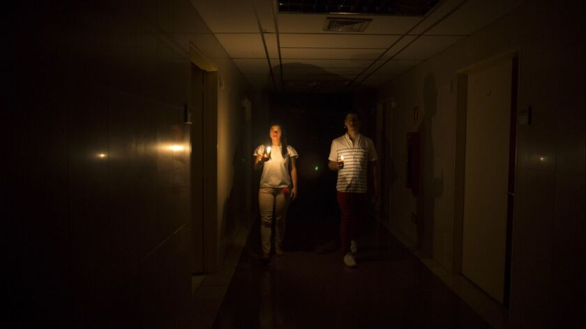 Relatives of a patient walk in the darkened hall of a clinic with a candle lighting the way, during