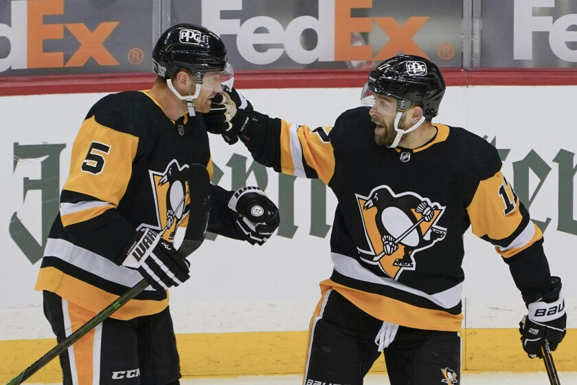 Pittsburgh Penguins' Bryan Rust (17) celebrates Wirth Mike Matheson (5) after getting an assist from him on a goal against the Washington Capitals during the first period of an NHL hockey game, Sunday, Feb. 14, 2021, in Pittsburgh. (AP Photo/Keith Srakocic)