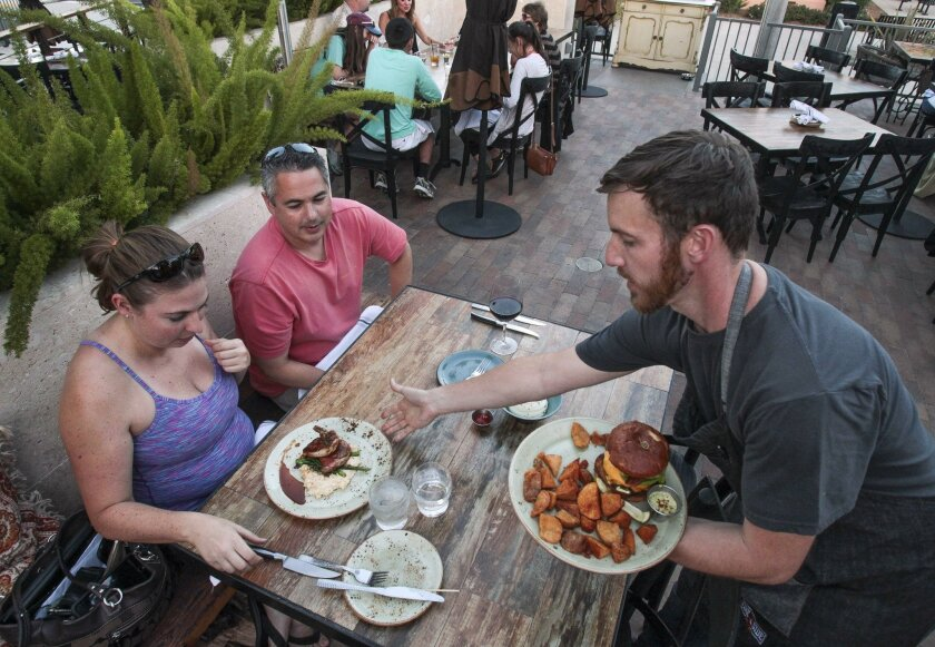 Kevin Crooks serves food to customers at Fireside by the Patio restaurant at Liberty Station in San Diego on Tuesday. Restaurant owner Gina Champion-Cain hasn't decided what changes she'll make to cover increased costs from minimum wage boost but she won't eliminate tipping.