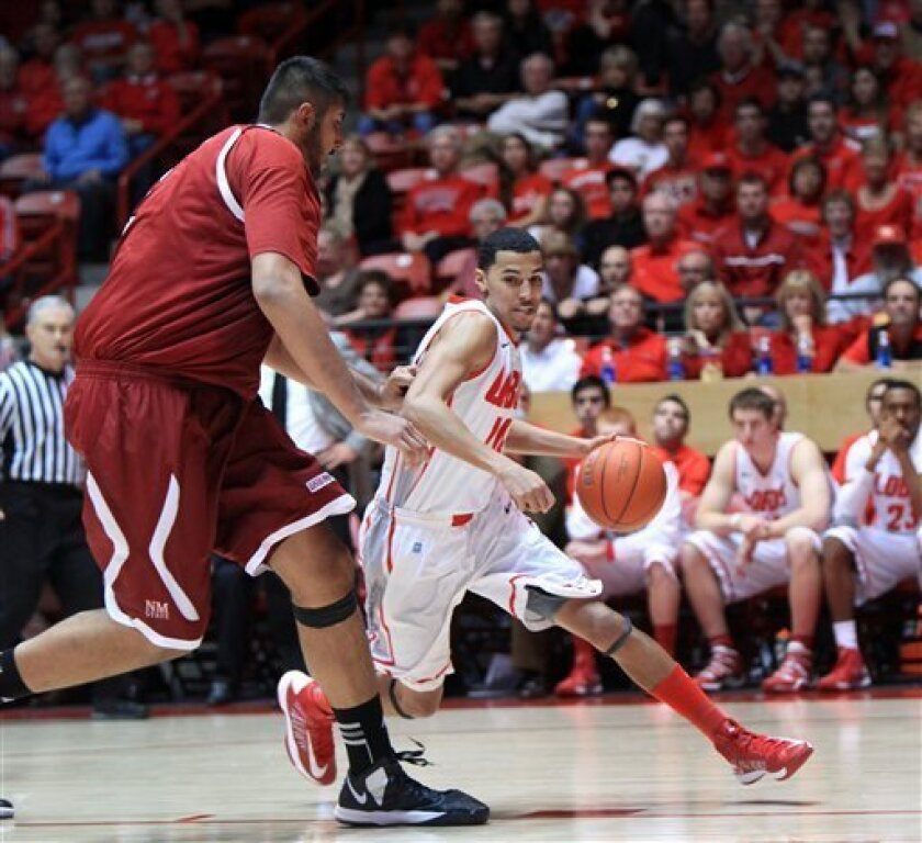 New Mexico's Kendall Williams drives around New Mexico State's Sim Bhullar in the second half of an NCAA college basketball game at The Pit in Albuquerque, N.M. Saturday, Dec. 15, 2012. New Mexico won 73-58. (AP Photo/Eric Draper)