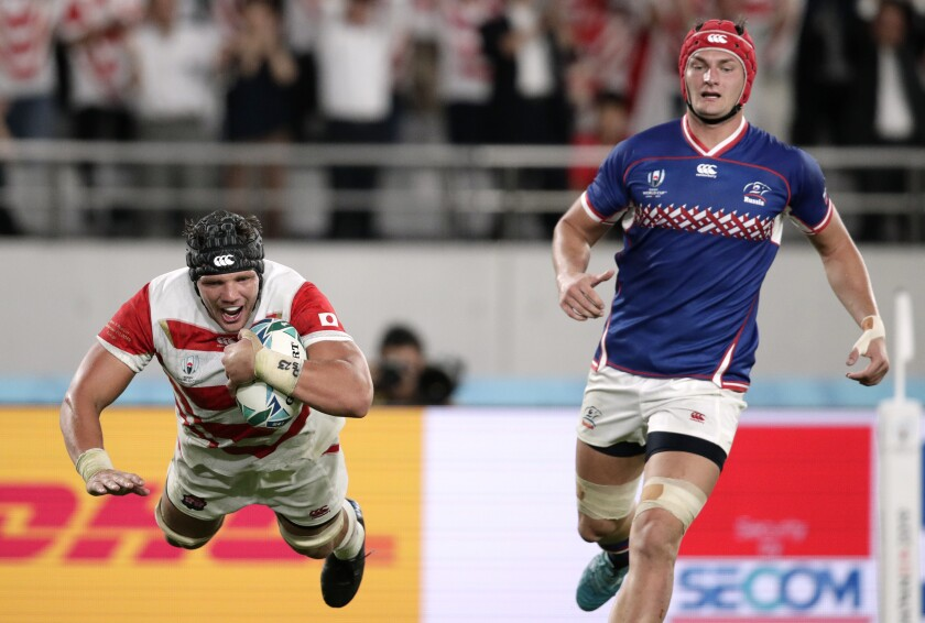 Japan's Pieter Labuschagne, left, is airborne as he scores a try as Russia's Bogdan Fedotko, right, watches during the Rugby World Cup Pool A game at Tokyo Stadium between Russia and Japan in Tokyo, Japan, Friday, Sept. 20, 2019. (AP Photo/Jae Hong)