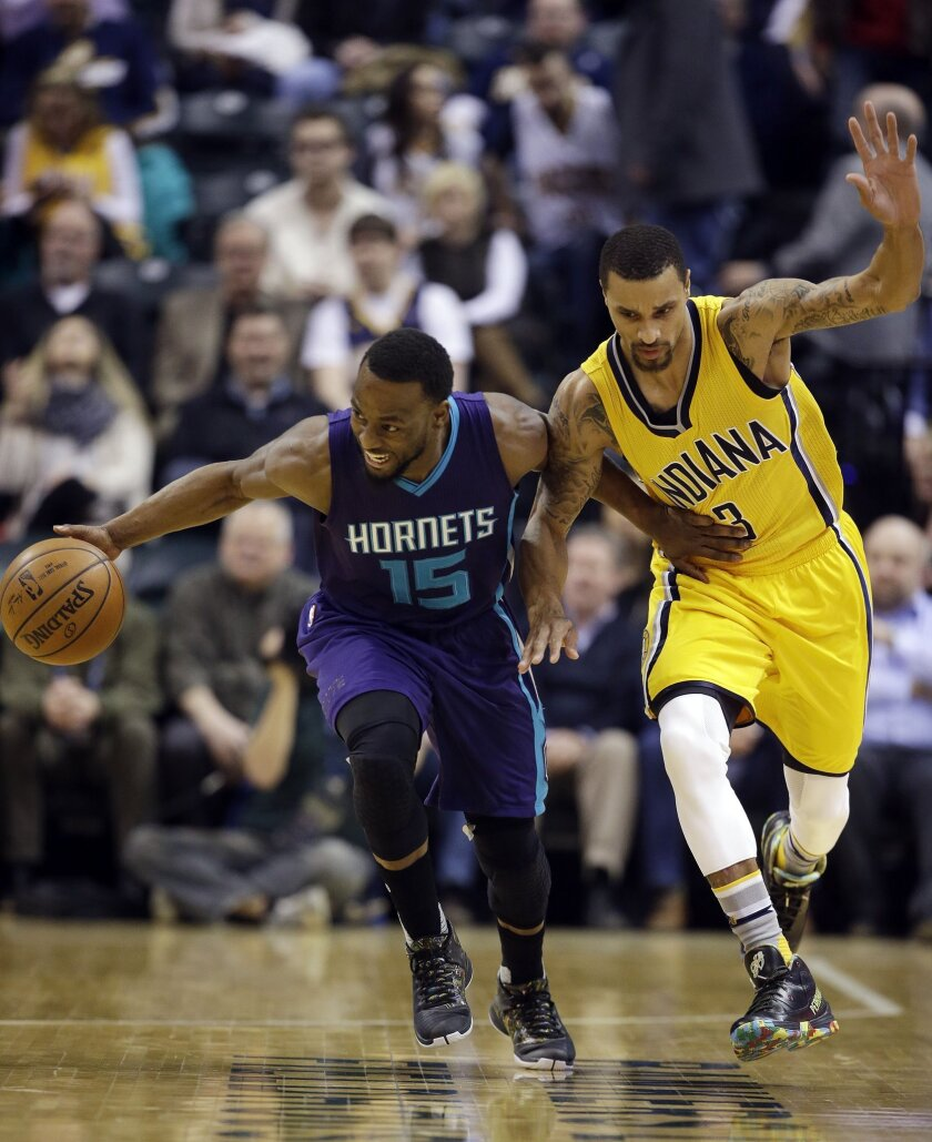 Charlotte Hornets' Kemba Walker (15) is defended by Indiana Pacers' George Hill (3) during the first half of an NBA basketball game Wednesday, Feb. 10, 2016, in Indianapolis. (AP Photo/Darron Cummings)