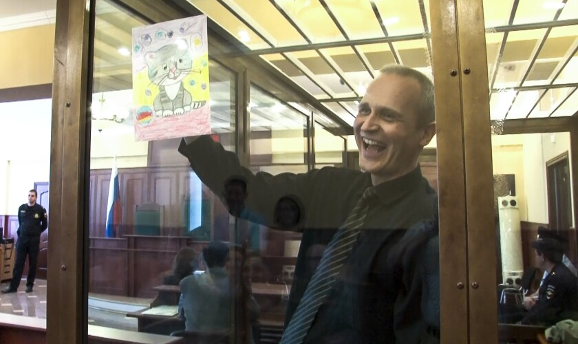 FILE In this file image taken from video, on Thursday, May 23, 2019 Dennis Christensen shows a picture in a court room in Oryol, Russia, Thursday, May 23, 2019. Two Jehovah's Witnesses were convicted of extremism in Russia and four more arrested, one of whom reported being tortured in custody. Russia officially banned Jehovah's Witnesses in 2017 and declared the group an extremist organization. Crackdown on the group has intensified since then. (AP Photo, File)
