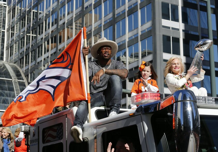 Super Bowl MVP and Denver Broncos linebacker Von Miller holds a Denver Broncos flag while Annabel Bowlen, wife of Denver Broncos owner Pat Bolwen hoists the Lombardi Trophy during a parade for the NFL football Super Bowl champions, Tuesday, Feb. 9, 2016, in Denver. (AP Photo/Jack Dempsey)