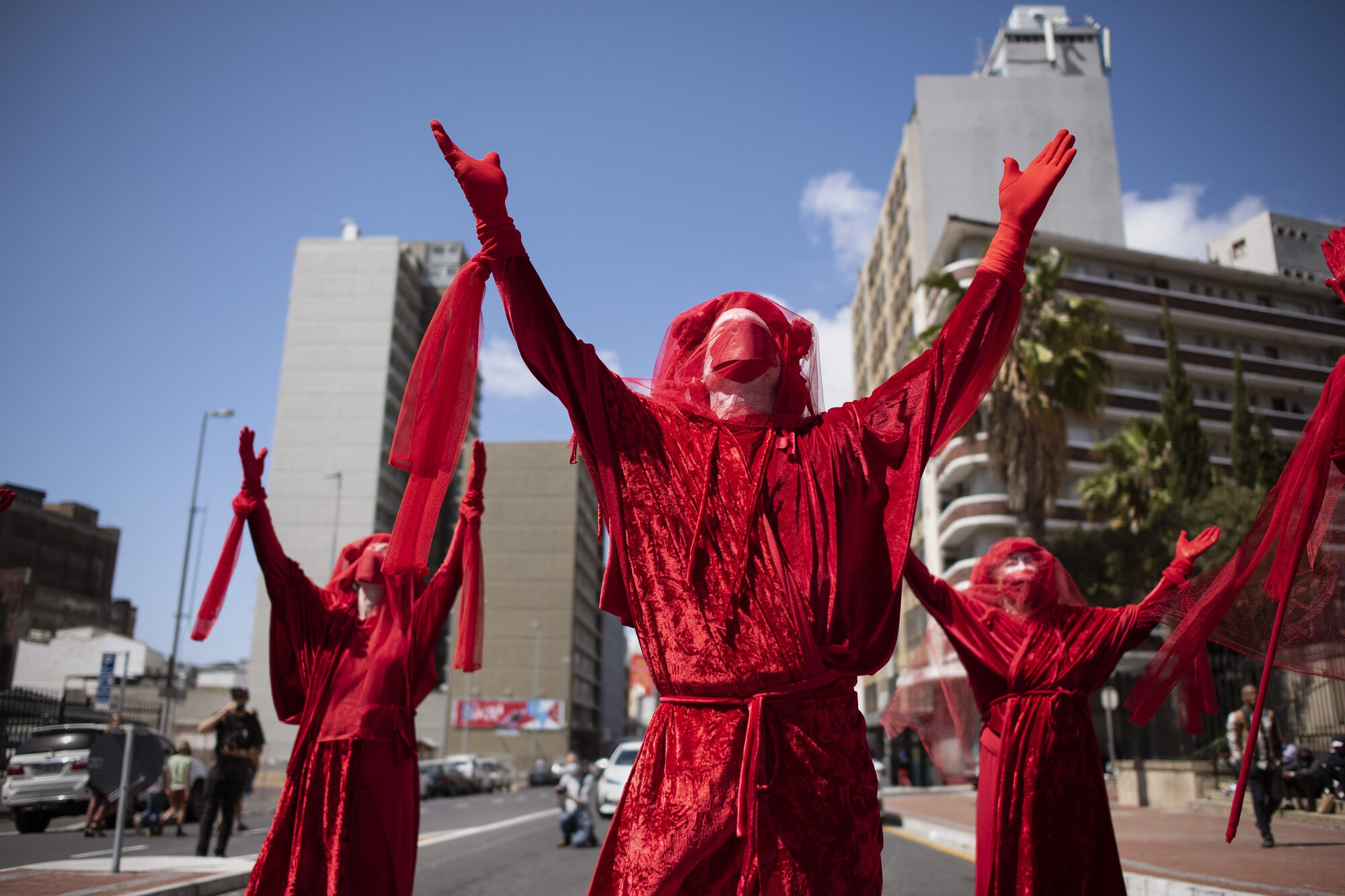 Outdoors, three people dressed in red lift their arms to the sky.