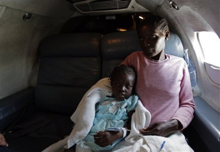 Five-year-old Betina Joseph, sits with her mother Denise Exima in a private jet while being evacuated to Children's Hospital in Philadelphia by the Boston-based aid group Partners in Health from Port-au-Prince, Sunday, Jan. 31, 2010. Doctors skirted a bureaucratic logjam to save the life of Joseph, who developed tetanus from a small cut on her thigh, and two more critically ill children, victims of Haiti's earthquake, flying them to U.S. hospitals on a private jet to avoid a military suspension of medical evacuation flights. (AP Photo/Andres Leighton)