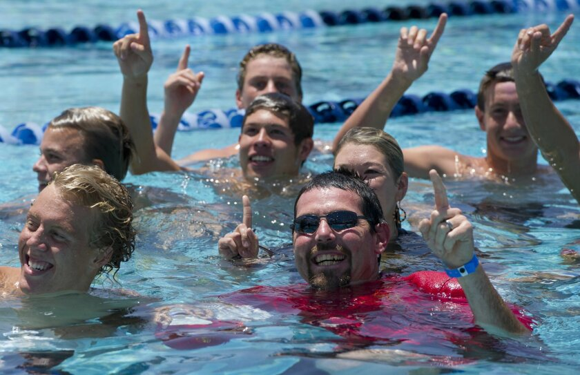 Mt. Carmel Swim Coach Dan Peck, in red, celebrates in the pool with his boys team after they won the San Diego Section Division II Swimming Championship on Saturday, May 18th, 2013.