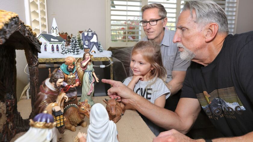 Craig Coley speaks to 3 year old Keira Andrew about the Christmas nativity scene decorations he recently set up in his living room. Above is Keira's grandfather Mike Bender, an investigator and former police officer whose efforts led to Craig's release fr