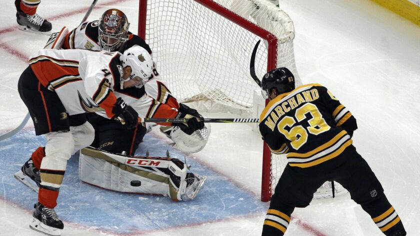 Ducks goaltender John Gibson makes a save as defenseman Hampus Lindholm (47) helps defend against a shot by Boston Bruins left wing Brad Marchand (63) in the first period.