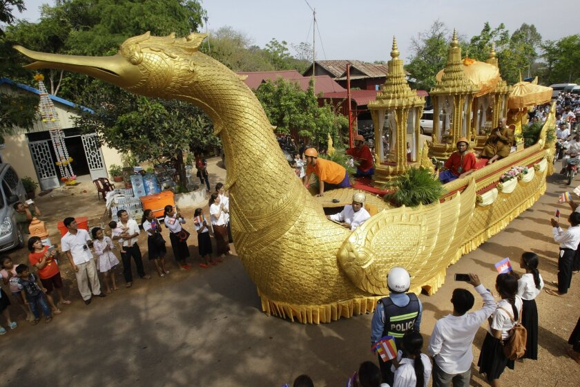 A chariot carrying a golden urn makes its way during a procession in Oudong, Kandal province, northwest of Phnom Penh, Cambodia, Friday, May 20, 2016. Thousands of Cambodians joined a procession to return what they believe are Buddha's relics to a mountain-top shrine from where they were stolen three years ago. (AP Photo/Heng Sinith)
