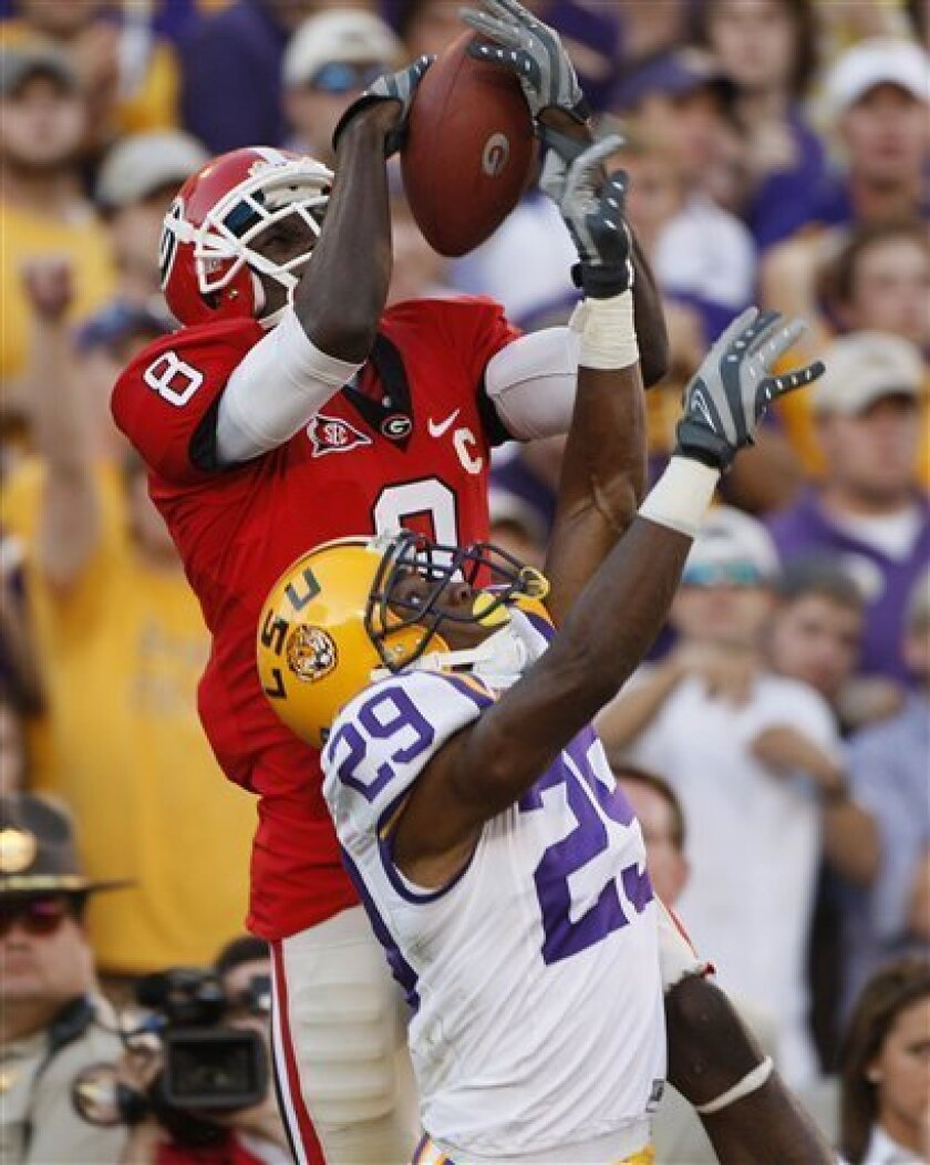 FILE - Iin this Oct. 3, 2009, file photo, Georgia's A.J. Green (8) makes a catch for a touchdown over LSU's Chris Hawkins during the fourth quarter of an NCAA college football game in Athens, Ga. When Georgia's A.J. Green goes up to make one of those amazing catches, it doesn't seem all that tough. No wonder. When you're able to juggle while riding a unicycle, being one of the nation's top receivers is a breeze. (AP Photo/John Bazemore, File)
