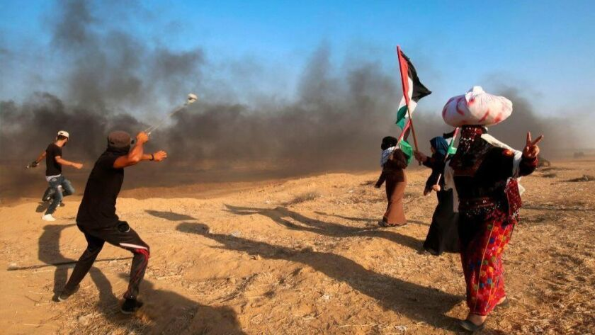 Palestinian protesters throw stones at Israeli forces during a demonstration at the Israel-Gaza border on Friday.