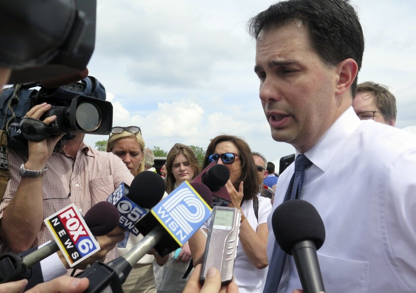 Wisconsin Gov. Scott Walker speaks with the media at a campaign appearance Thursday, June 12, 2014, in Oak Creek, Wis. Walker, who is running for re-election this year and eyeing a bid for president in 2016, said that his personal opposition to same-sex marriage doesn't matter because the ban on gay marriage was put into the state constitution by a vote of the people. A federal judge last week struck down the state's ban on same-sex marriages. (AP Photo/Carrie Antlfinger)