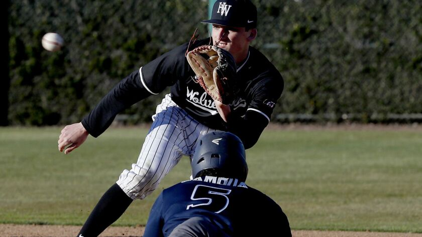 Harvard-Westlake shortstop Tyler Cox prepares to receive a throw and tag out Birmingham pinch-runner Daniel Gamboa a game between top-25 opponents on Feb. 19.