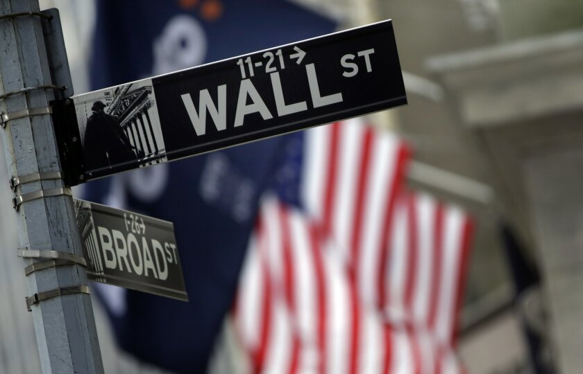 FILE - This Thursday, Oct. 2, 2014, file photo, shows a Wall Street sign adjacent to the New York Stock Exchange. U.S. stocks are bouncing back early Thursday, May 12, 2016, as companies, including agribusiness giant Monsanto, are climbing on reports of possible buyouts. Retailers got more bad news