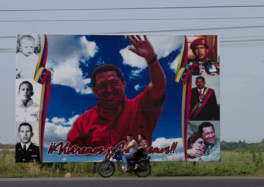 In this Tuesday, Nov. 24, 2015 photo, a couple ride past a billboard welcoming visitors, designed with images of Venezuela's late President Hugo Chavez, in Sabaneta, Venezuela. Opposition candidates are venturing into towns where they've been absent for more than a decade, including Sabaneta, where the Chavez brothers lived during their early childhood. (AP Photo/Fernando Llano)