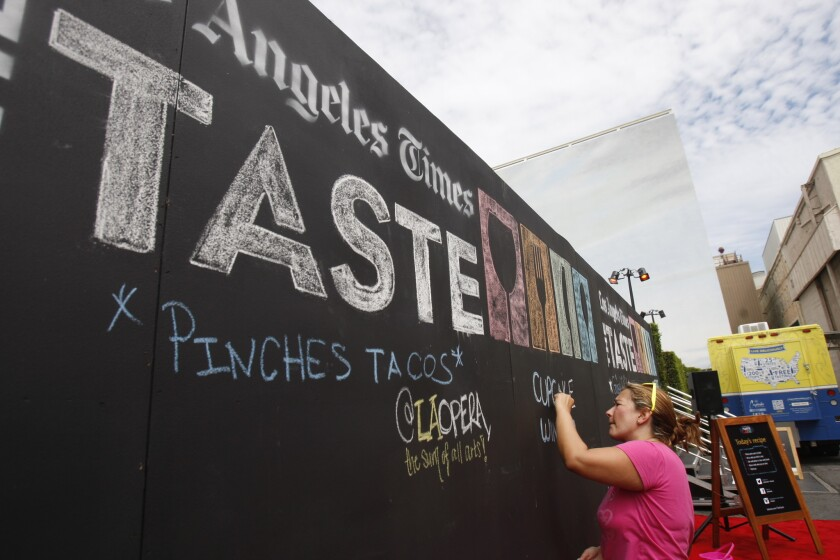 "Helga Oliveros draws on the ""What are you tasting?"" wall at the 2013 event."