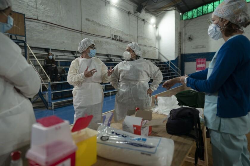 La supervisora de enfermería Paola Almirón, centro derecha, organiza una campaña de vacunación contra el COVID-19 en un gimnasio en las afueras de Buenos Aires, Argentina, el viernes 9 de julio de 2021. (AP Foto/Víctor R. Caivano)