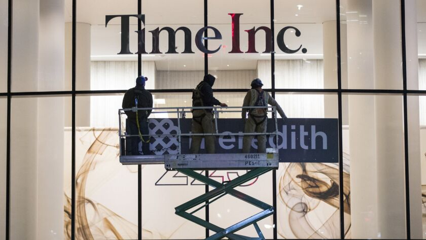 Workers prepare to cover up Time Inc. signage with Meredith Corp. signage in New York on Jan. 31.
