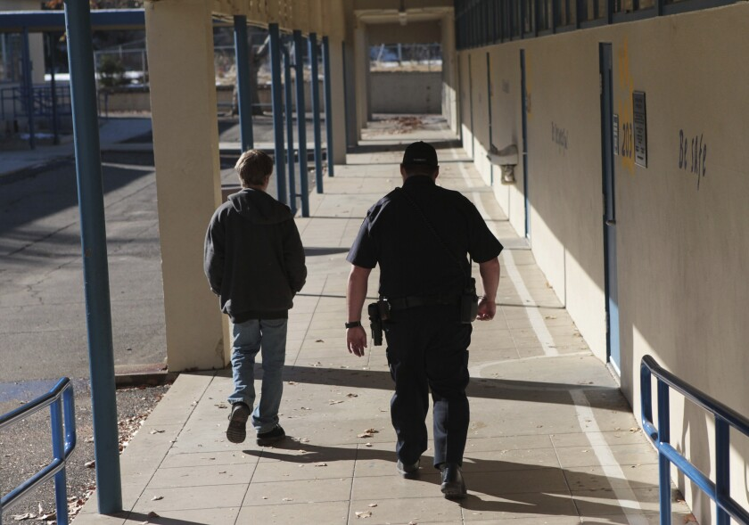In this Dec. 9, 2013, file photo, a school resource officer in Anderson, Calif., walks a middle school student back to class.