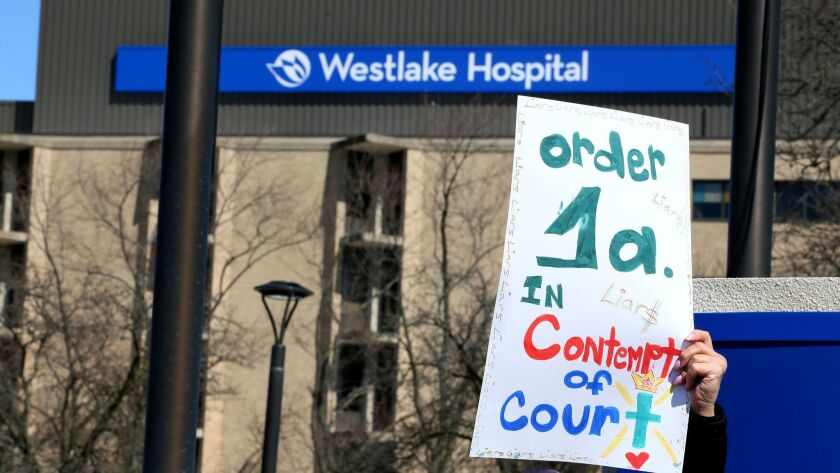 A worker holds a sign alleging a contempt of court violation by Westlake Hospital during a protest a