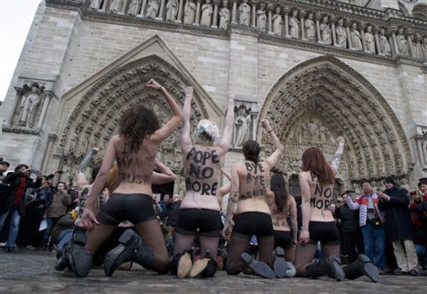 Activists of the Women's Movement FEMEN, protest against Pope Benedict XVI who announced his resignation yesterday,  in Notre Dame Cathedral, Paris, Tuesday, Feb. 12, 2013.  (AP Photo/Michel Euler)
