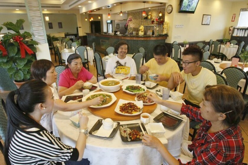 Seated at Taste of Chong Qing Sichuan restaurant in San Gabriel are Sarah Du, left, co-owner Linda Huang, Jing Chen, master chef Qing Jiang, chef Liang Gang, waiter Criss Cai and co-owner Xiao Wen Turner.