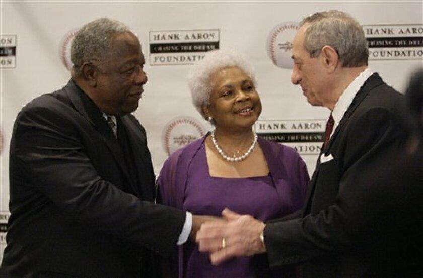Hank Aaron, left, shakes hands with Mario Cuomo, as Aaron's wife Billye Aaron looks on during a celebration of Aaron's 75th birthday, Thursday Feb. 5, 2009, in Atlanta. (AP Photo/John Amis)