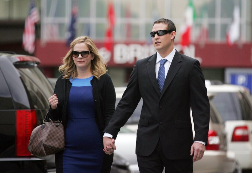 Christopher Hays (right) holds hands with his wife, Erika Hays, as they go to court on Tuesday in San Diego. Hays, a San Diego police officer who was accused of misconduct on duty, pleaded not guilty to sexual battery and false imprisonment charges involving four women.