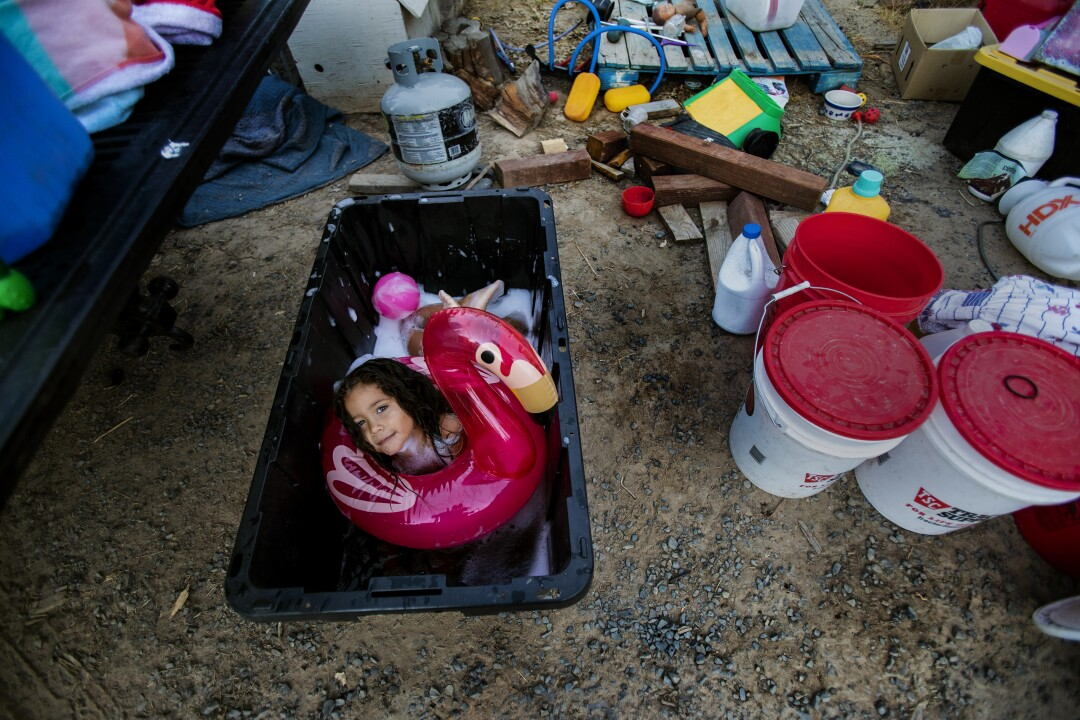 A little girl plays with an inflatable flamingo inside a bin filled with water.