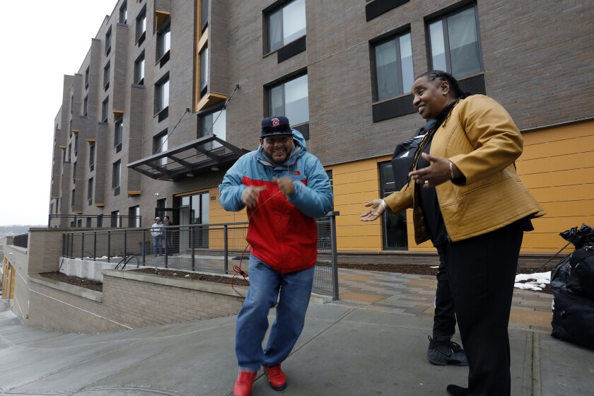 Jesus Melendez, 46, left, rushed to move his belongings into his studio apartment at Landing Road, a new shelter and long-term housing facility in the Bronx, where Marguerite Brown welcomes him and other new residents.