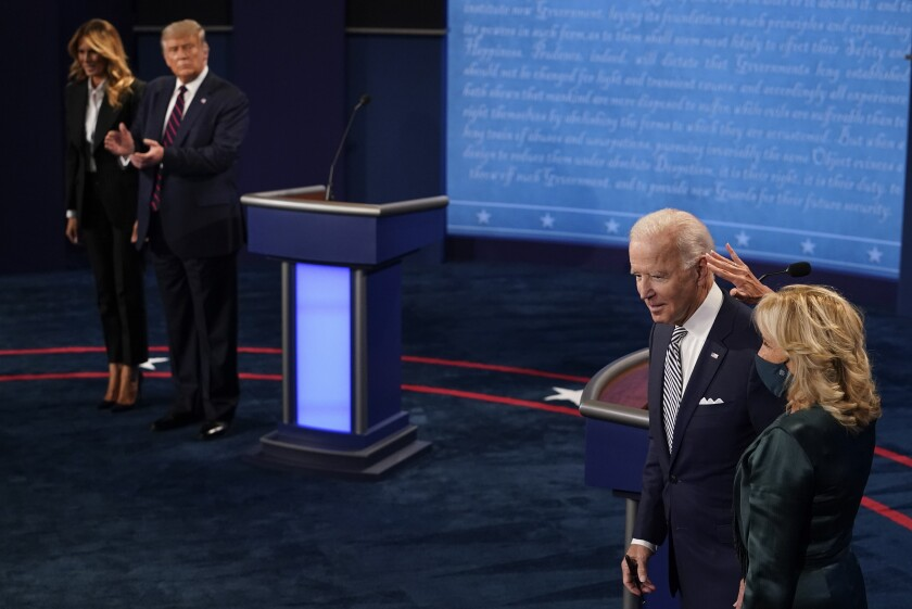 First lady Melania Trump stands with President Donald Trump as he looks at Democratic presidential candidate former Vice President Joe Biden and his wife Jill Biden during the first presidential debate Tuesday, Sept. 29, 2020, at Case Western University and Cleveland Clinic, in Cleveland, Ohio. (AP Photo/Morry Gash, Pool)