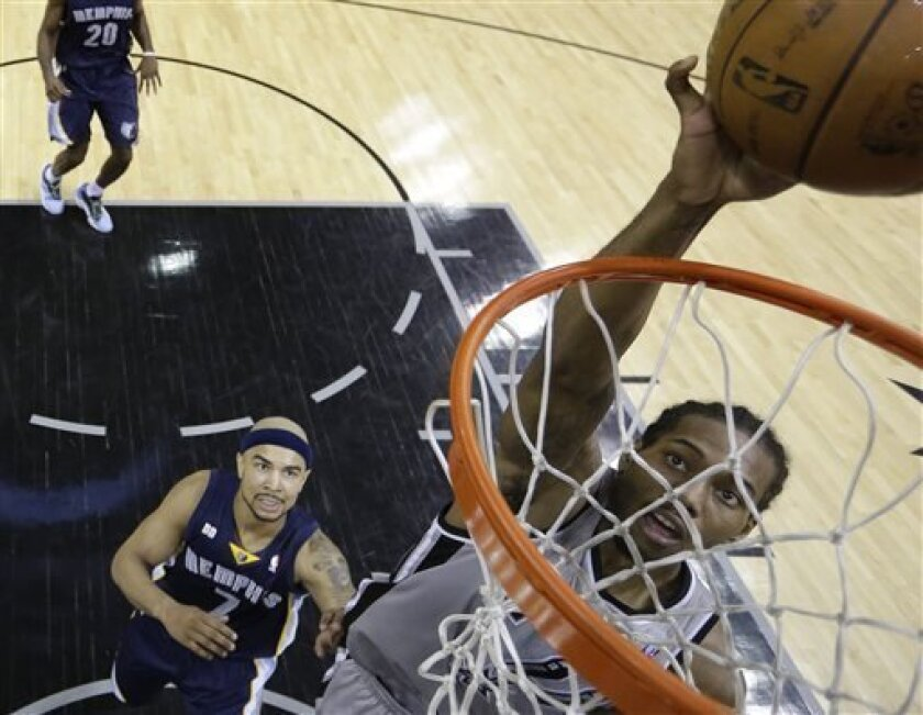 San Antonio Spurs' Kawhi Leonard, right, scores as Memphis Grizzlies' Jerryd Bayless (7) looks on during the second half in Game 1 of a Western Conference Finals NBA basketball playoff series, Sunday, May 19, 2013, in San Antonio. The Spurs won 105-83. (AP Photo/Eric Gay)