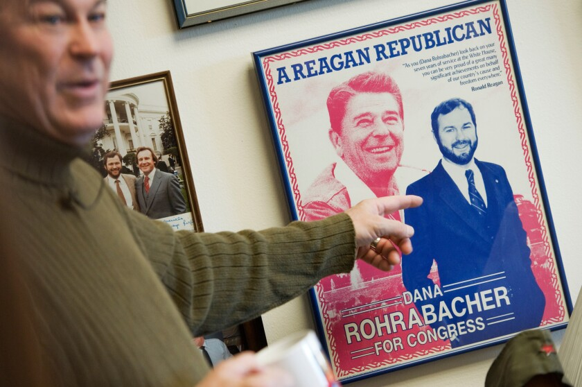 Rep. Dana Rohrabacher (R-Huntington Beach) points at a campaign poster with his image alongside Ronald Reagan's while giving a tour of his Washington office.