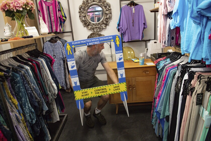 Retailer Clive Williams installs a protective screen in his Pop Up Clothing Company store, in Stratford-upon-Avon, Warwickshire, England, Sunday, June 14, 2020. Lockdown restrictions are slowly being eased, which should see the economy start to pick up. On Monday, nonessential shops, such as department stores and electronic retailers, can reopen if they can abide by social distancing requirements. (Jacob King/PA via AP)