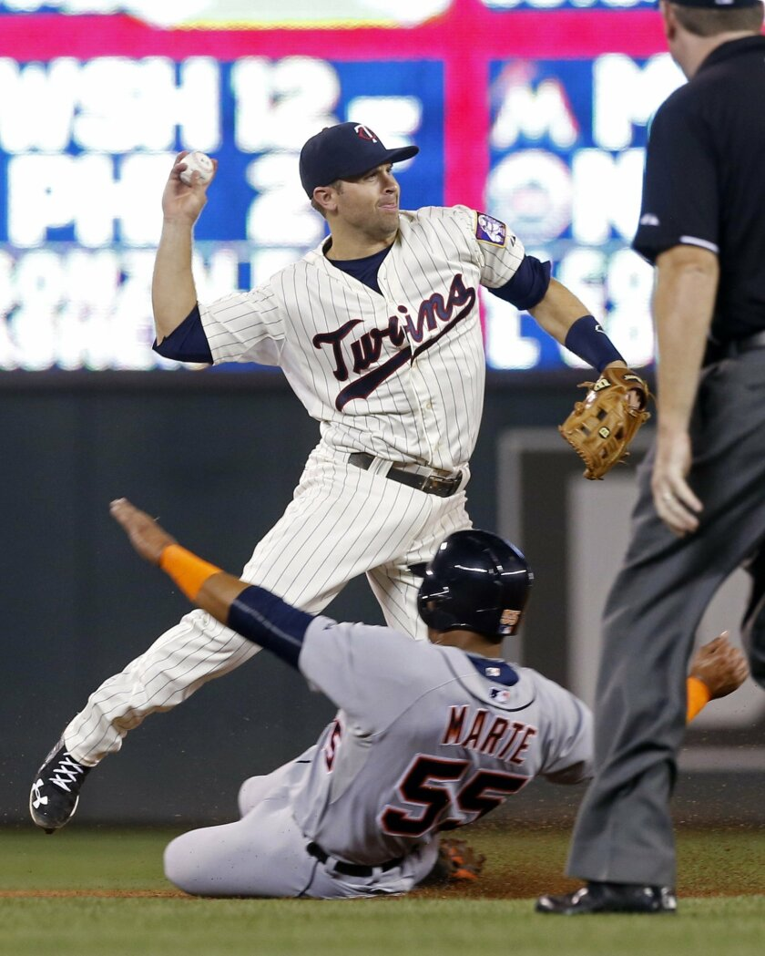 Minnesota Twins second baseman Brian Dozier throws to complete the double play on Detroit Tigers' James McCann after the force at second of Jefry Marte, bottom, in the fourth inning of a baseball game, Wednesday, Sept. 16, 2015, in Minneapolis. (AP Photo/Jim Mone)