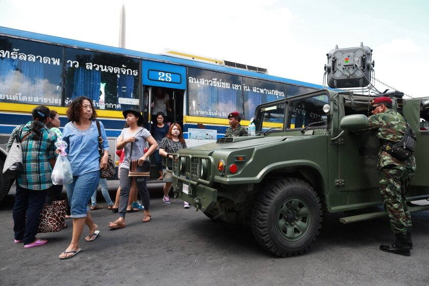 "Thai soldiers stand guard near their vehicle as bus passengers walk past in Bangkok's Victory Monument, Thailand, Sunday, June 8, 2014. Thai police warned online critics of the military junta Friday that they will ""come get you"" for posting political views that could incite divisiveness, the latest reminder about surveillance of social media in post-coup Thailand. (AP Photo/Wason Wanichakorn)"