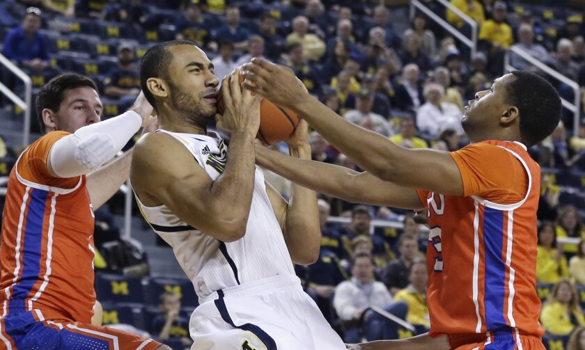 Houston Baptist center Cody Stetler, left, and guard Tyler Russell, right, reach in on Michigan forward Jon Horford (15) during the first half of an NCAA college basketball game in Ann Arbor, Mich., Saturday, Dec. 7, 2013. (AP Photo/Carlos Osorio)