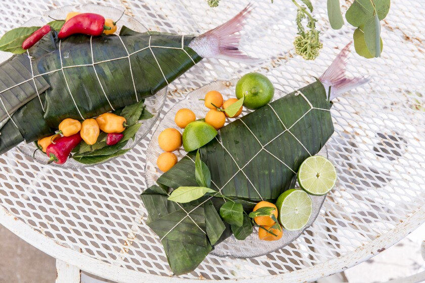 Only the tails can be seen of two fish wrapped in banana leaves, one on a plate with citrus; the other, with peppers.