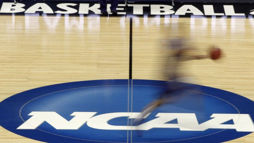 FILE - In this March 14, 2012, file photo made with a long exposure, a player runs across the NCAA l