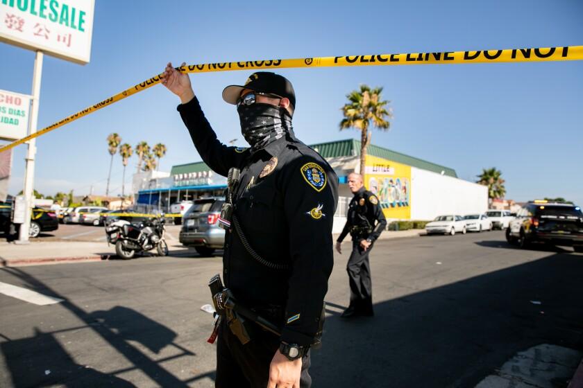 San Diego police officers stand on Menlo Avenue near El Cajon Boulevard