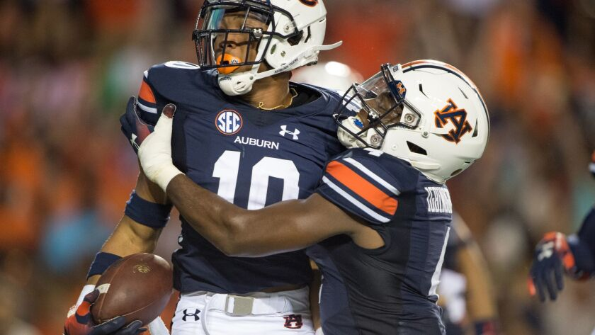 Auburn running back Devan Barrett (10) celebrates with wide receiver Noah Igbinoghene (4) after scoring a touchdown against the Alabama State in the second quarter on Sept. 8 in Auburn, Ala.