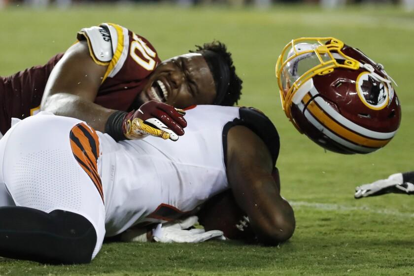 Washington linebacker Josh Harvey-Clemons loses his helmet as he tackles Cincinnati receiver Auden Tate.