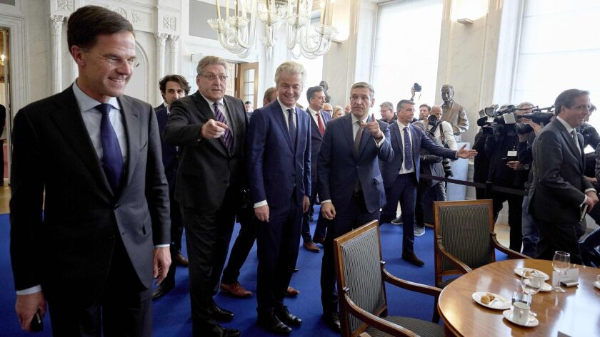 Dutch Prime Minister Mark Rutte, left, and Dutch PVV leader Geert Wilders, center, arrive for a meeting.