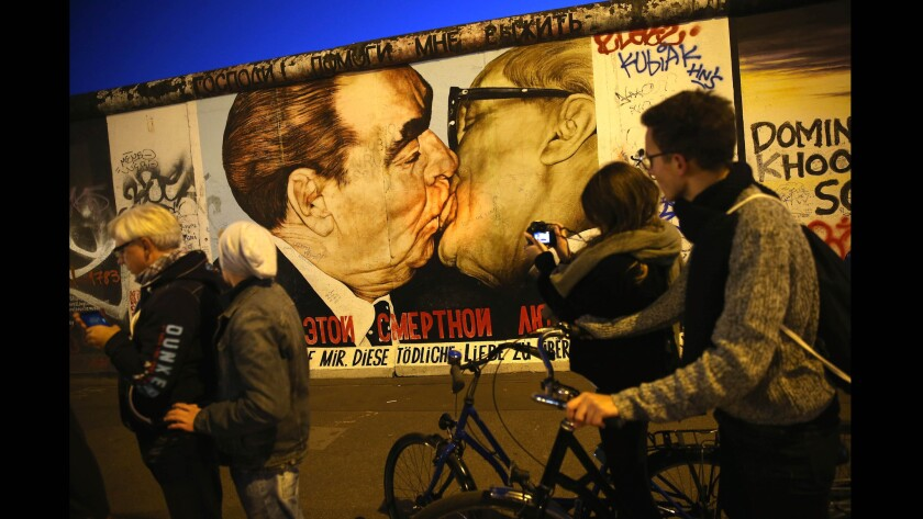 Visitors gather Oct. 28, 2014, at a mural showing former Soviet leader Leonid Brezhnev, left, kissing former East German communist leader Erich Honecker at the East Side Gallery, a section of the Berlin Wall that today is a tourist attraction.