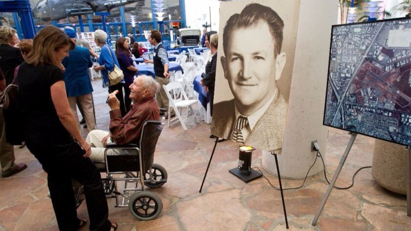 Bill Gibbs, in his wheelchair, talked to a guest at his 100th birthday party at the San Diego International Air & Space Museum in October, 2010.  Next to him is a photo of Gibbs in his younger days.